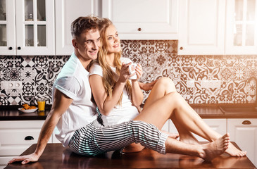 Happy romantic couple sitting on the table at the kitchen and looking to the window