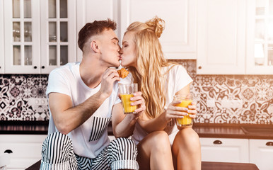 Romantic couple holding orange juice and kiss each other