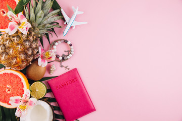 Traveler accessories and tropical fruits on trendy pink background. Bright summer color. Flat lay and top view