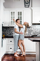 Lovely beautiful couple standing and hugging on a kitchen at home