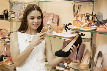 Young woman taking a photo of high heels at the store