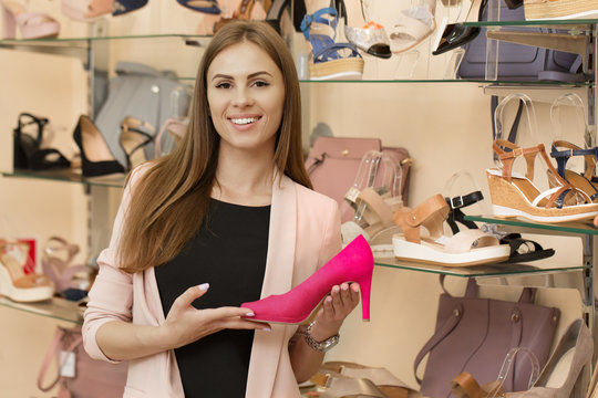 Cheerful shop assistant working at the shoe shop