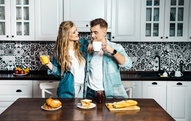 Romantic couple having breakfast at the light kitchen