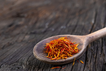 Saffron in a spoon on a dark wooden background, focus, macro shot, Blossom, cooking.