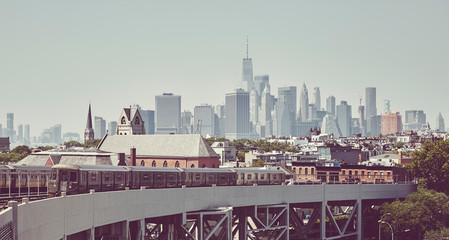 Retro toned picture of a subway train with New York City skyline, USA.