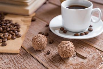 Coffee time break. Cup of freshly breved turk coffee, chocolate balls and book on wooden table