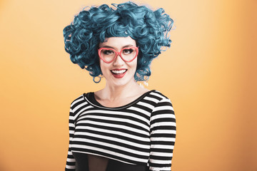 Fun portrait of pretty Asian woman with bright blue wig and red heart shaped glasses