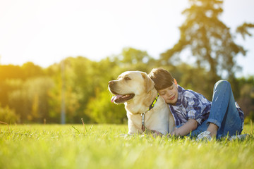 Young cheerful boy resting at the park with his dog