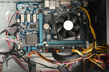 view into an open computer, desktop pc tower with motherboard, cooler and cables