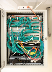 network server cabinet with racks, cables, optical lines, ethernet switches and a wireless router in the data room of a school