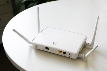 wireless internet router with connection for ethernet and console on a white table in the office, copy space, selected focus, narrow depth of field