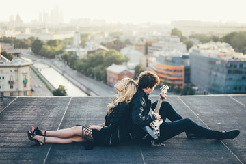 Couple in rock-n-roll style siting on the rooftop and relax at the sity background. Man playing on guitar.