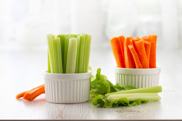 Vegetarian healthy food concept. Green celery, lettuce leaves and carrot.