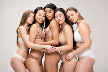 five multiethnic dreamy girls with closed eyes hugging and leaning on each other isolated on grey, body positivity concept