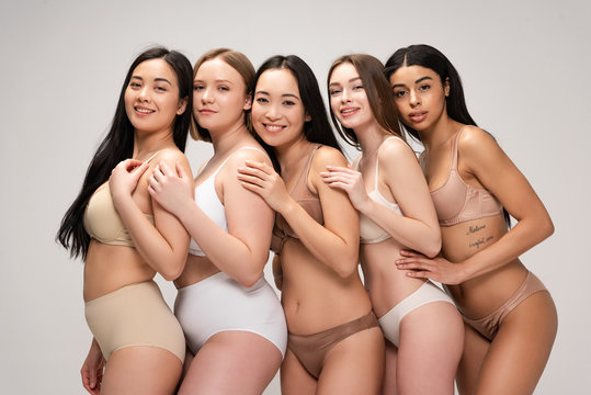 five happy young woman embracing each other and smiling isolated on grey, body positivity concept