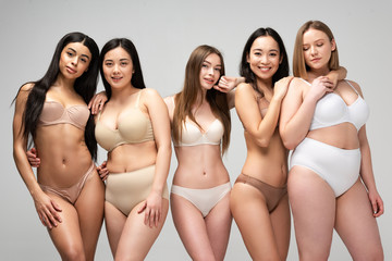 five attractive young multiethnic women in underwear posing at camera isolated on grey, body positivity concept