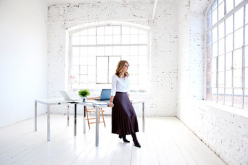 Attractive young creative woman standing at office desk and looking thoughtfully Wall mural