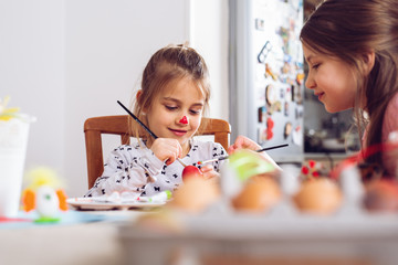 Happy easter. A beautiful child girl painting Easter eggs.
