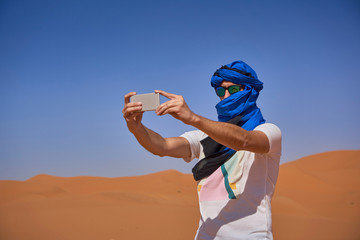 Morocco, man wearing sunglasses and blue tuban taking photo with smartphone in the desert
