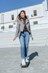 Portrait of smiling young woman standing on her skateboard