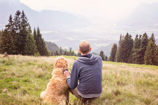 Austria, Tyrol, Kaiser mountains, man with dog on a hiking trip in the mountains