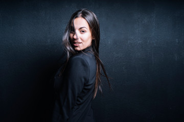 Portrait of young woman wearing black blazer in front of black background
