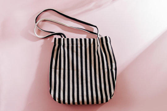 Striped cloth shopping bags on pink background.