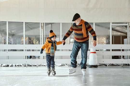 Grandfather and grandson on the ice rink, ice skating