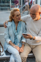 Spain, Barcelona, senior couple sitting at tram stop in the city sharing smartphone with earbuds