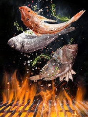 Tasty fishes flying above cast iron grate with fire flames. Freeze motion barbecue concept.