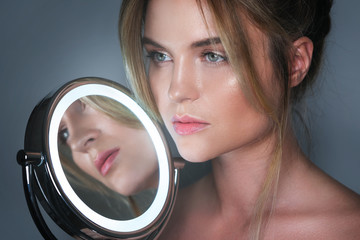 Woman and round mirror with LED light