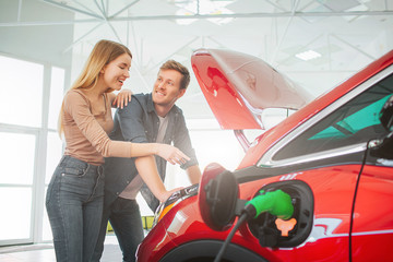 Young smiling family buying first electric car in the showroom. Attractive pleasantly surprised woman point at eco-friendly car battery while standing near her husband. Electric car sale concept