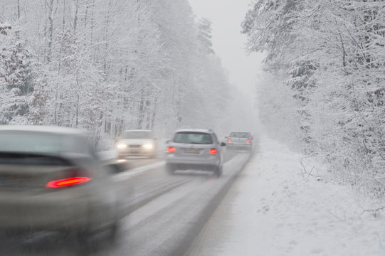 Cars driving on country road in winter, driving snow
