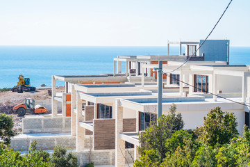Construction site on a sunny spring day, the construction of a complex of villas on the Adriatic coast. View of an unfinished building