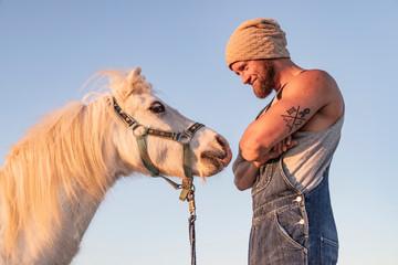 Smiling man facing pony under blue sky