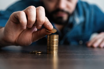 Business man putting a coin on coins stack saving bank and account for his money all in finance accounting concept.