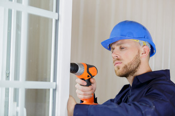 man drilling a hole in a window frame