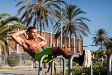 Barechested muscular man doing sit-ups outdoors