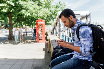 UK, London, man using his smartphone on the street