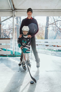Father and son on the ice rink, boy playing ice hockey