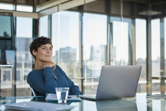 Smiling businesswoman sitting at desk in office with laptop