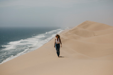 Namibia, Walvis Bay, Namib-Naukluft National Park, Sandwich Harbour, woman walking in dune landscape at the sea