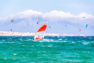 Spain, Andalucia, Tarifa, windsurfers and kite surfers on the sea with mountains of Morocco in the background