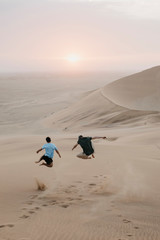 Namibia, Namib, back view of two friends jumping in the air on desert dune
