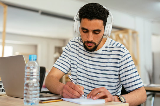 Young man wearing headphones taking notes at desk in office