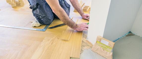 Obraz Fischgrät parkett verlegen. Arbeiter verlegt einelne stäbe in kleber bett - fototapety do salonu