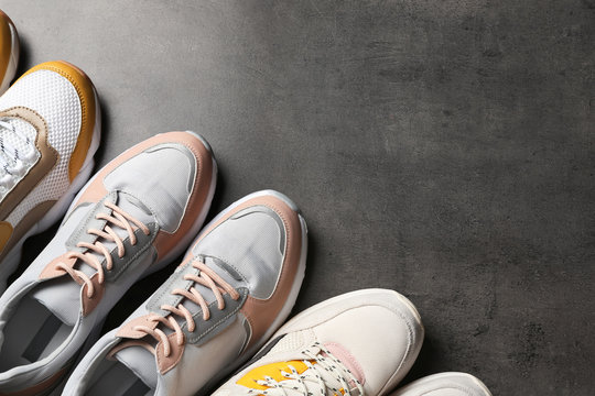 Flat lay composition with sneakers and space for text on grey background. Stylish shoes