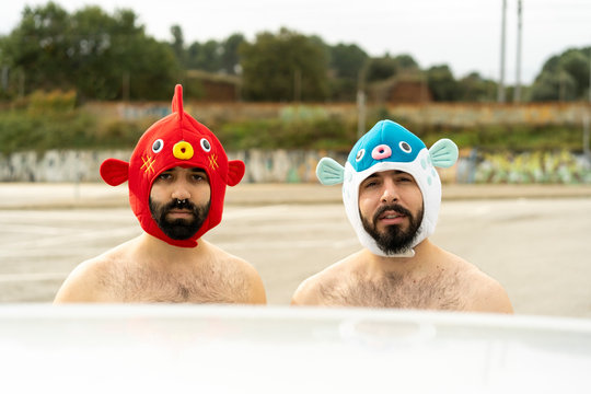 Portrait of shirtless gay couple wearing animal hats outdoors