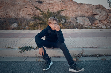 Blond teenager in black clothe sitting on street border