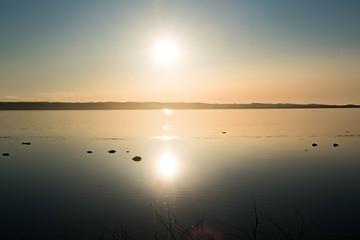 静かな湖に反射する夕日